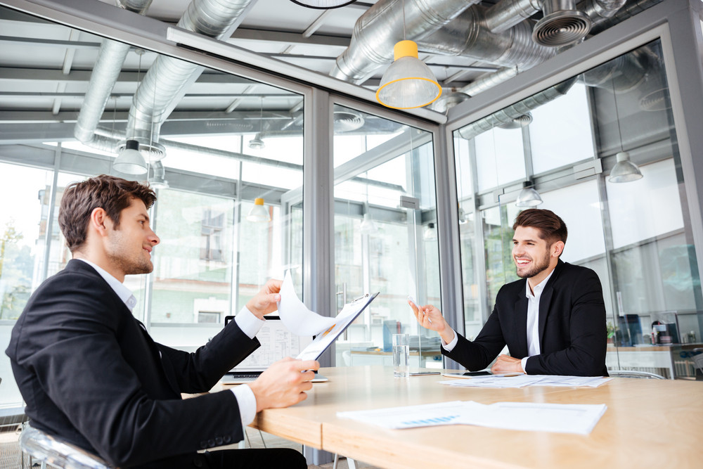 Two cheerful young businessmen creating business plan on meeting in office