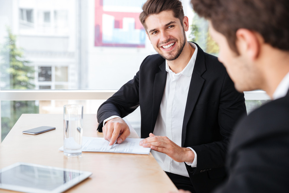 Two cheerful young businessmen talking and working with documents in office