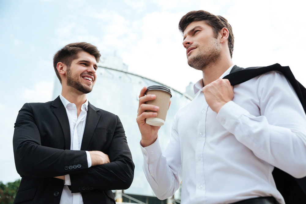 Two confident young businessmen talking and drinking coffee outdoors