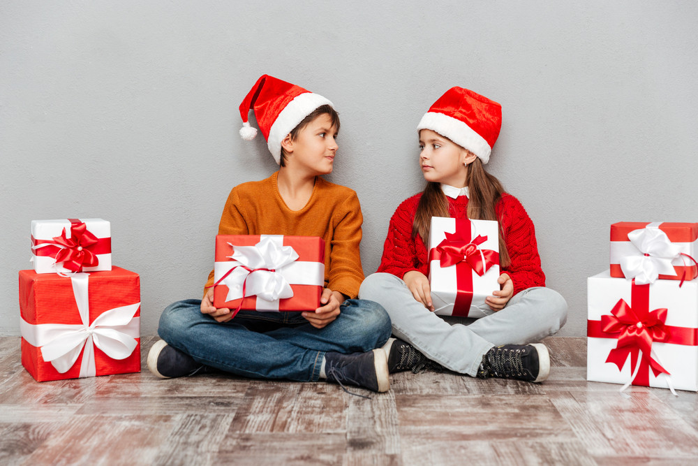 Two cute children in santa claus hats holding gift boxes