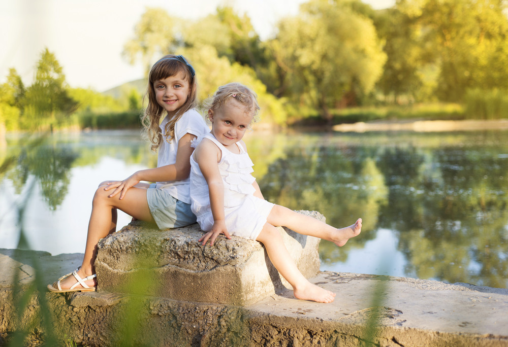 Two cute little sisters sittting by the lake