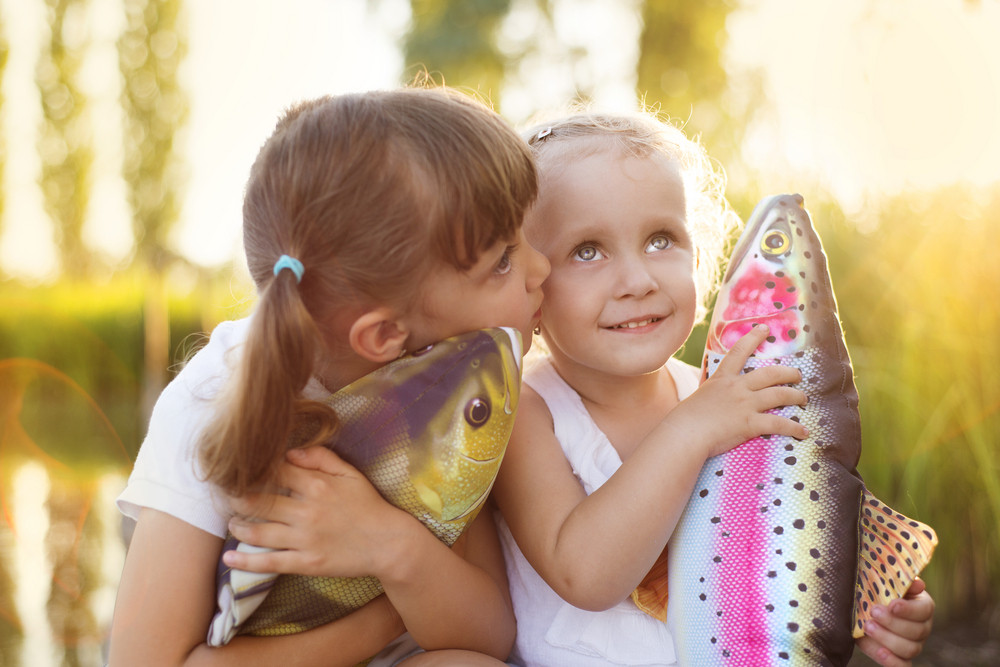 Two cute little sisters with playing with toy fish by the lake