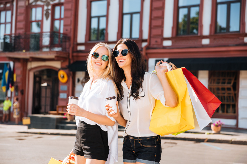 Two elegant happy women walking on the city street holding shopping bags