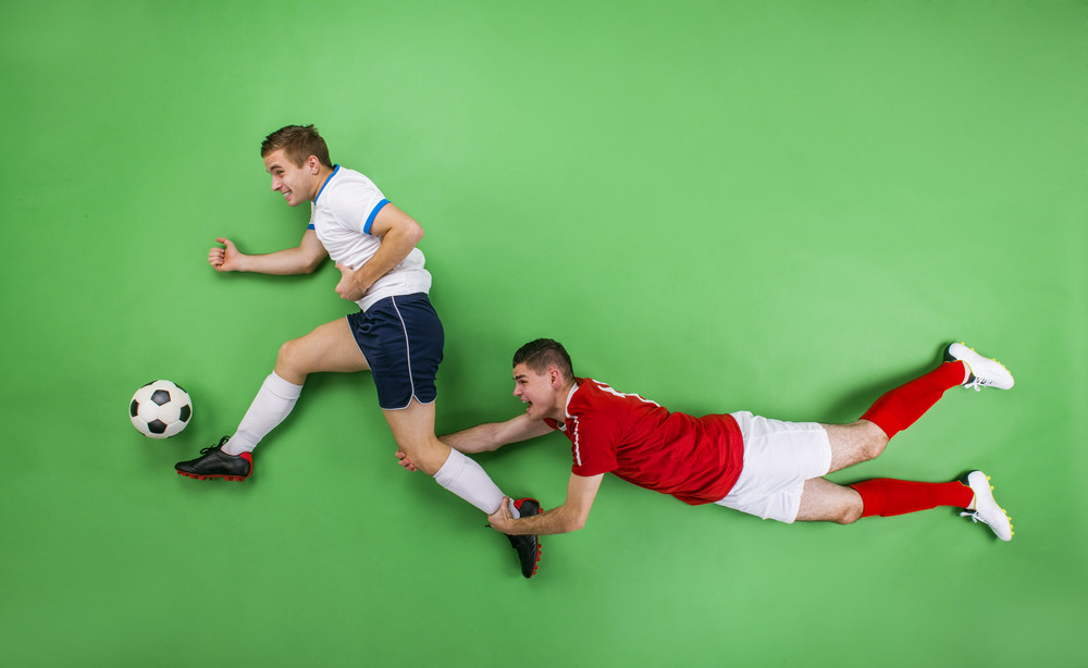 Two enthusiastic football players fighting for a ball. Studio shot on a green backgroud.