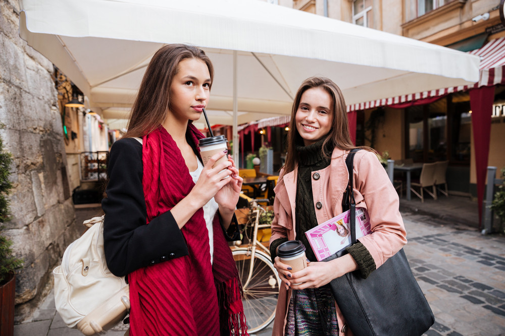 Two fashion models in coats on the street. smiling. drink coffee
