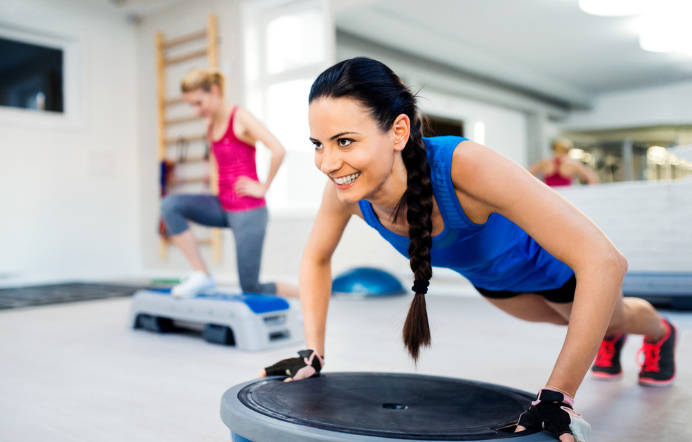 Two fit young attractive women in gym doing various exercises