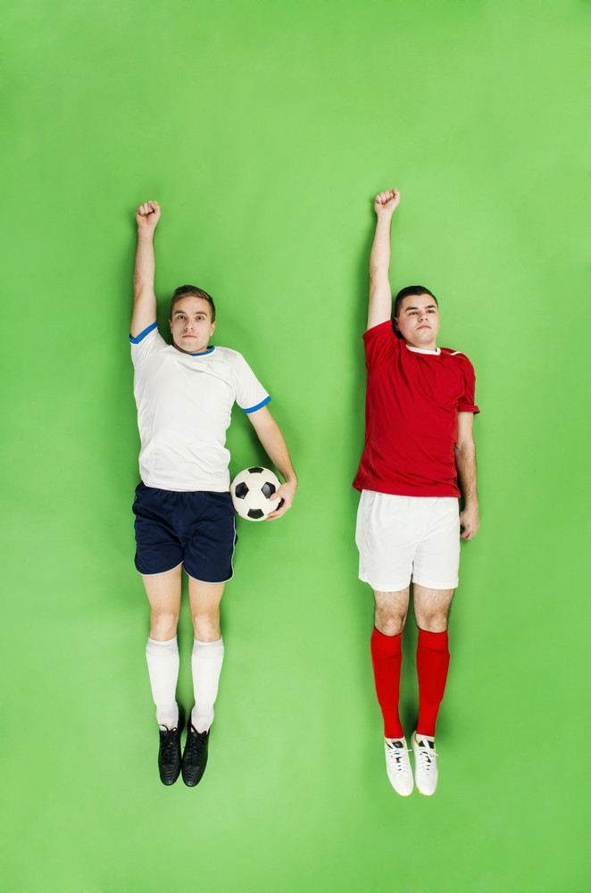 Two football players in a superman pose. Studio shot on a green backroung.