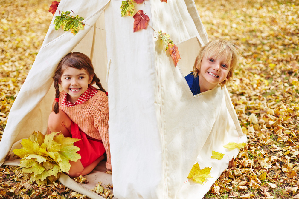 Two friendly kids sitting in tent in autumn park