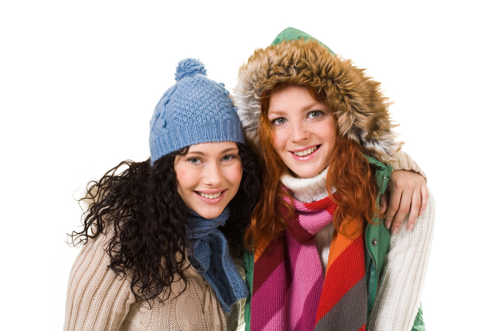 Two friends in warm knitted clothes looking at camera over white background