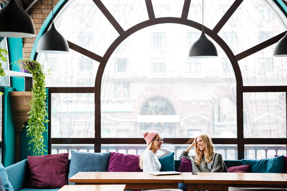 Two happy attractive young women sitting and talking in cafe