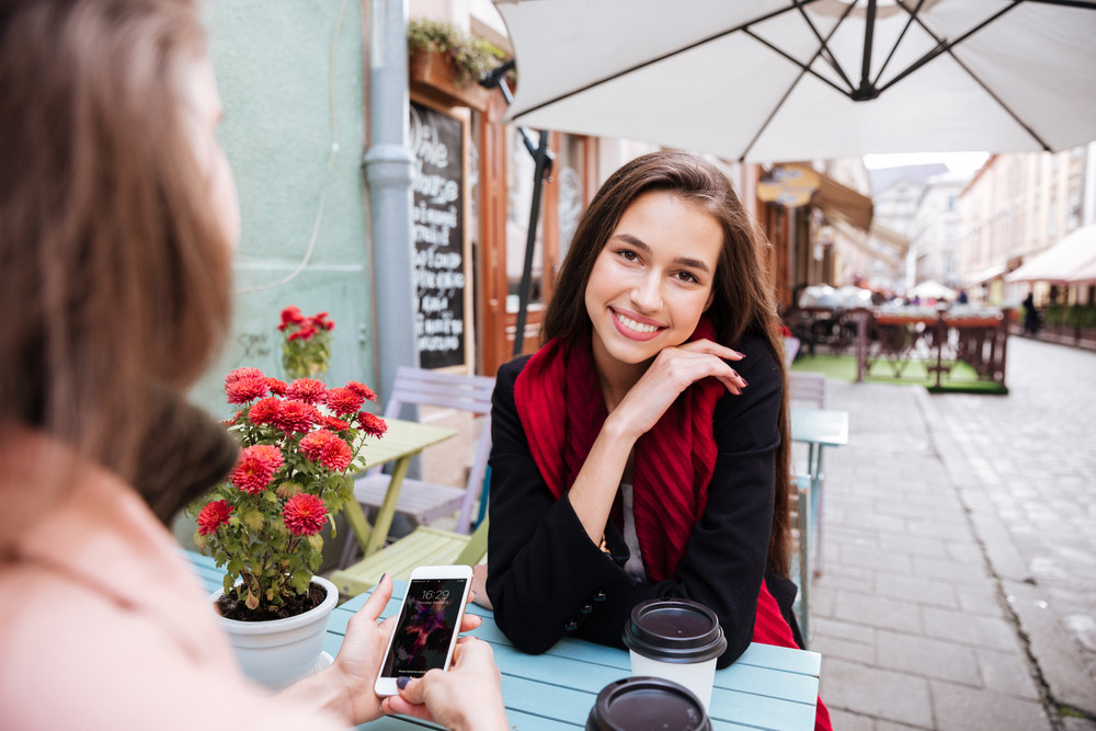 Two happy attractive young women talking and using cell phone in outdoor cafe