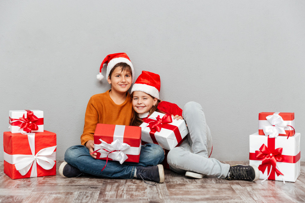 Two happy children in santa claus hats sitting and holding present boxes
