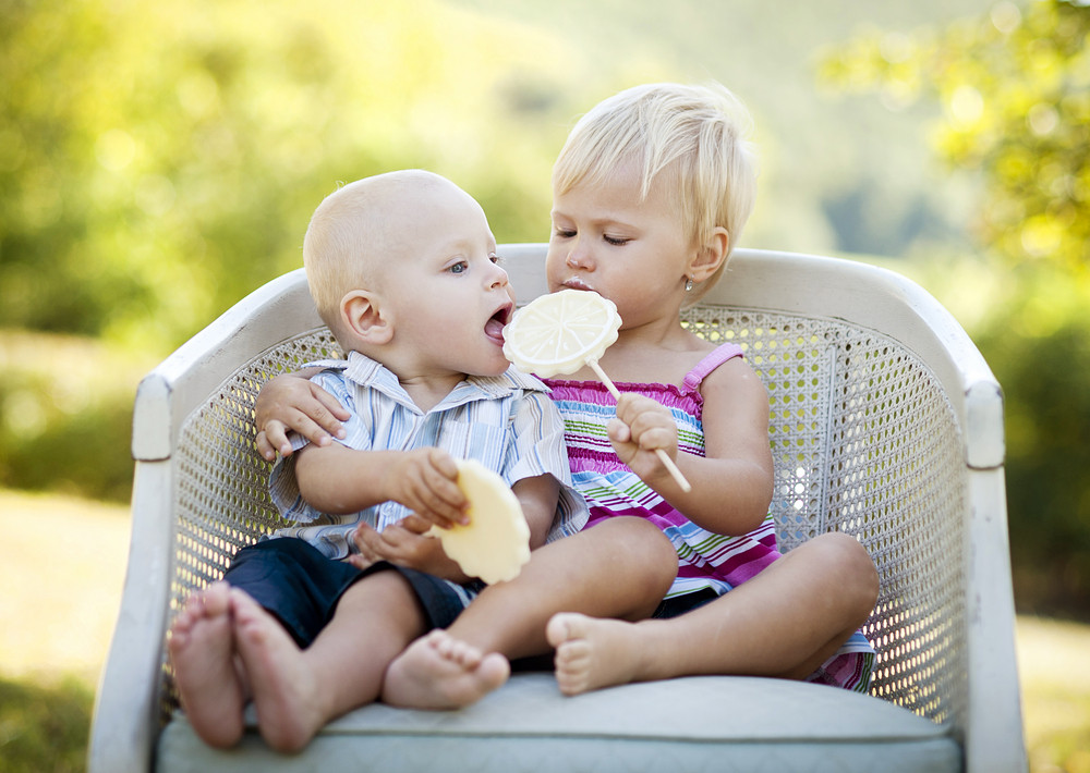 Two happy kids eating lolly in the park