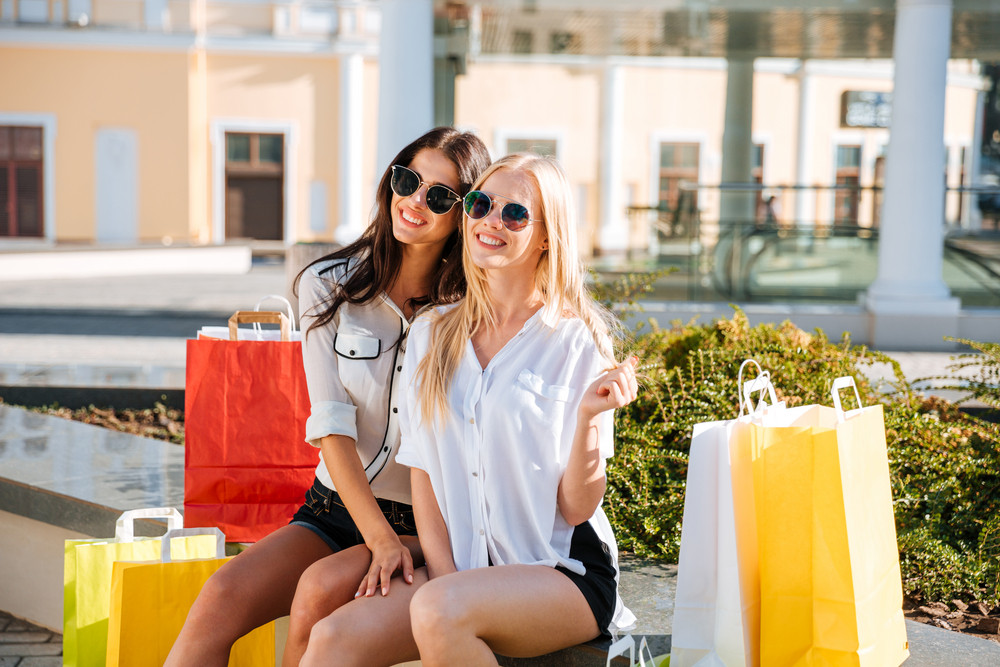Two happy smiling women sitting on bench with shopping bags and looking at camera