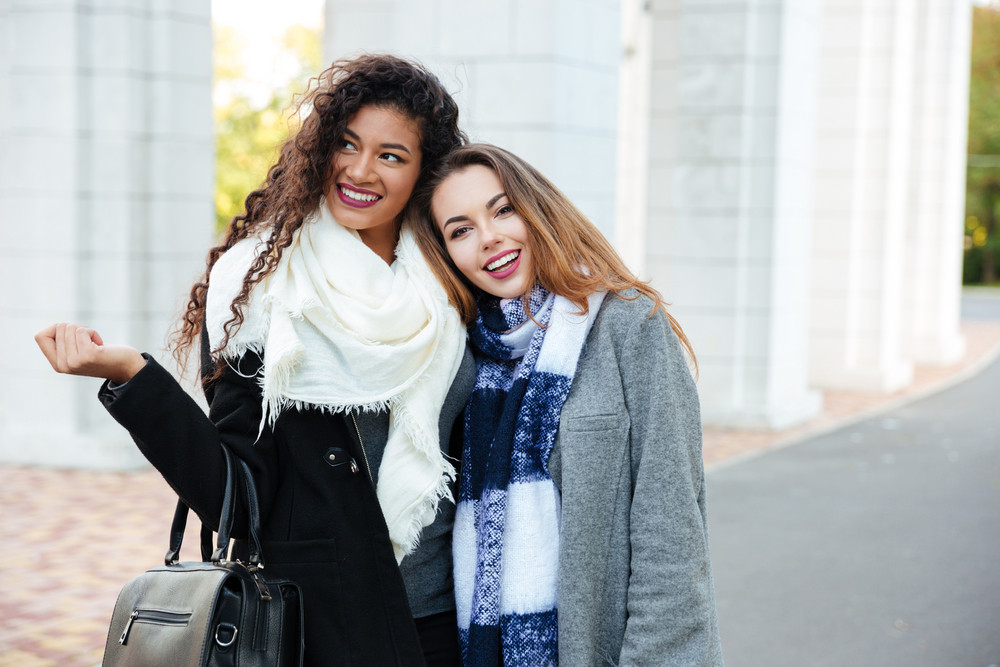 Two happy young ladies hugging on street background. Caucasian lady wearing scarf in a cage print looking at camera. African young curly woman wearing white big scarf and holding bag look aside.