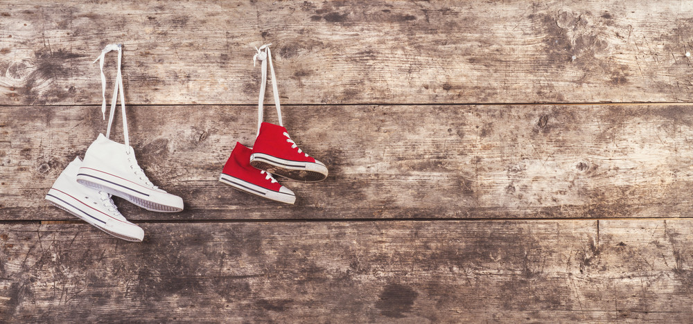 Two pairs of sports shoes hang on a nail on a wooden fence background