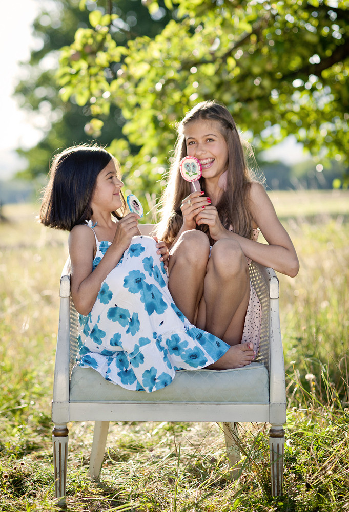Two sisters laughing and playing in green sunny park