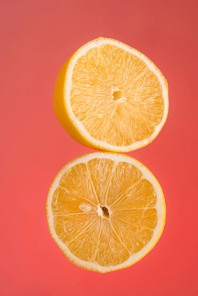 Two slices of fresh orange isolated on red background