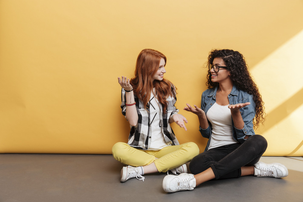 Two smiling confused young women sitting with legs crossed and talking over yellow background