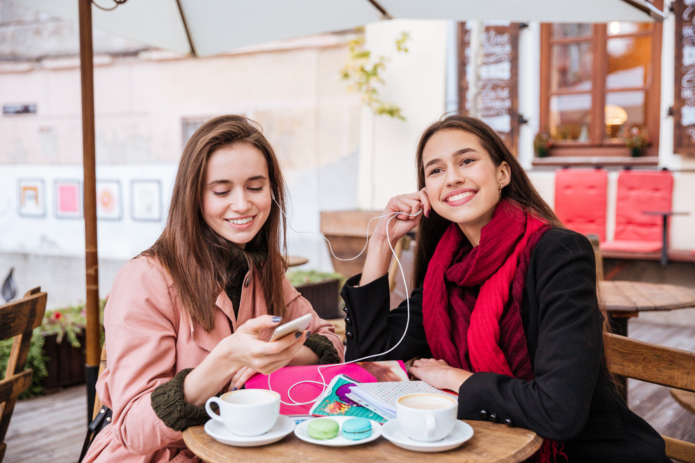Two smiling pretty young women with earphones listening to music from mobile phone in outdoor cafe