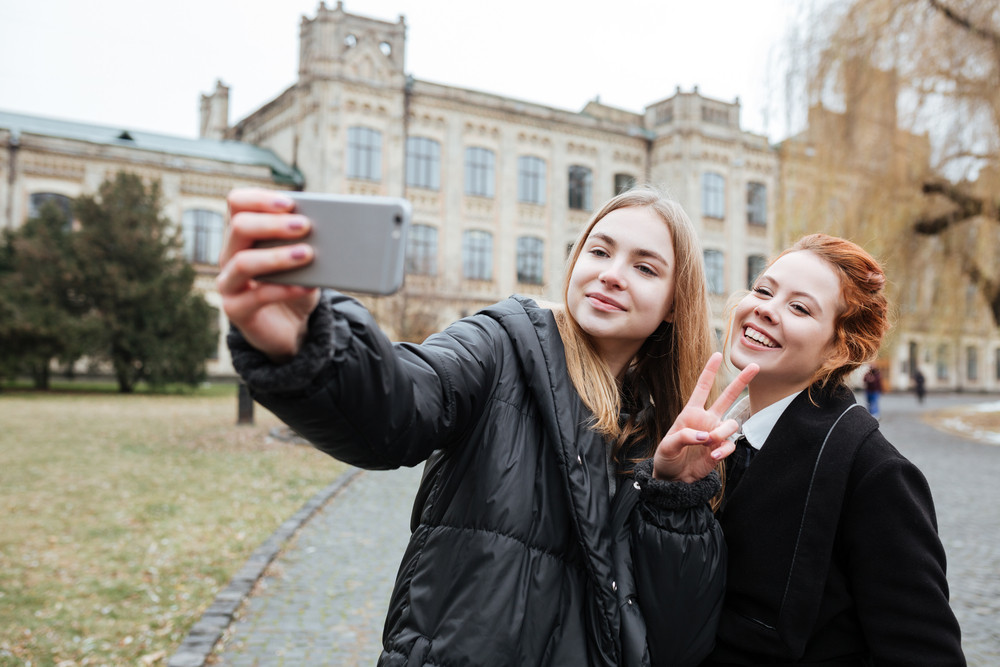 Two smiling young female students taking selfie outdoors with college building on background