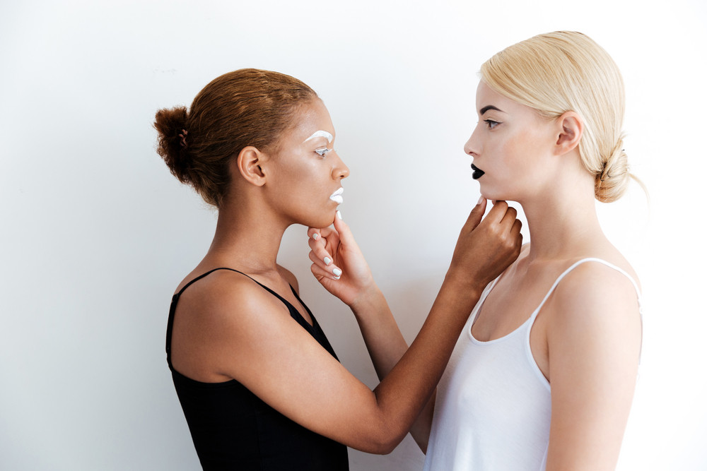 Two stylish young women with fashion makeup standing and touching chins af each other over white background