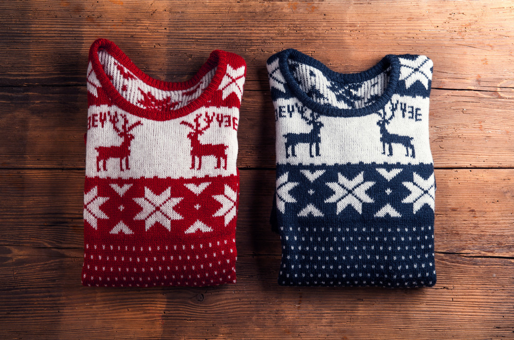 Two winter sweaters laid on a wooden table background