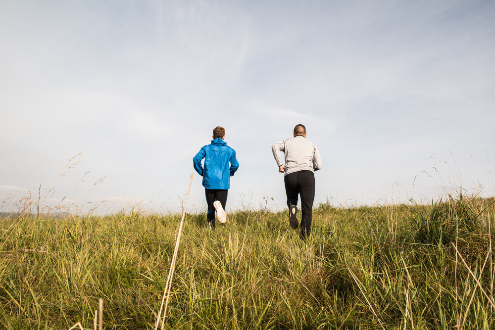 Two young athletes in sports jackets running in sunny autumn nature, rear view.