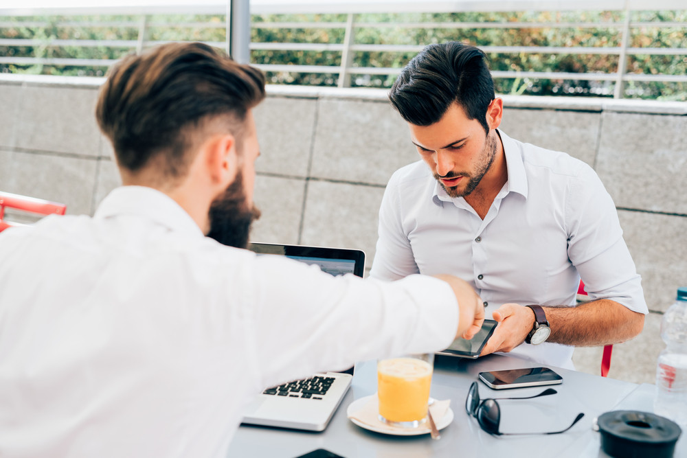 Two young bearded caucasian modern business man sitting in a bar, using tablet and laptop, looking downward, touching the screen - business, work, technology concept - focus on black hair man