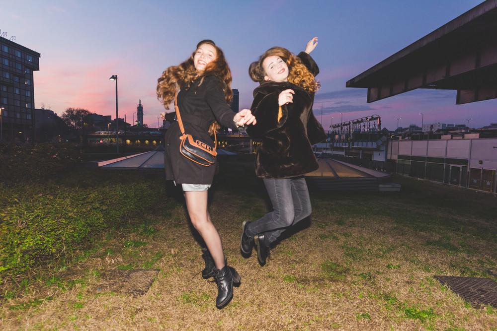 Two young beautiful caucasian women friends jumping outdoor at sunset, having fun - freedom, having fun, girl power concept - flash technique