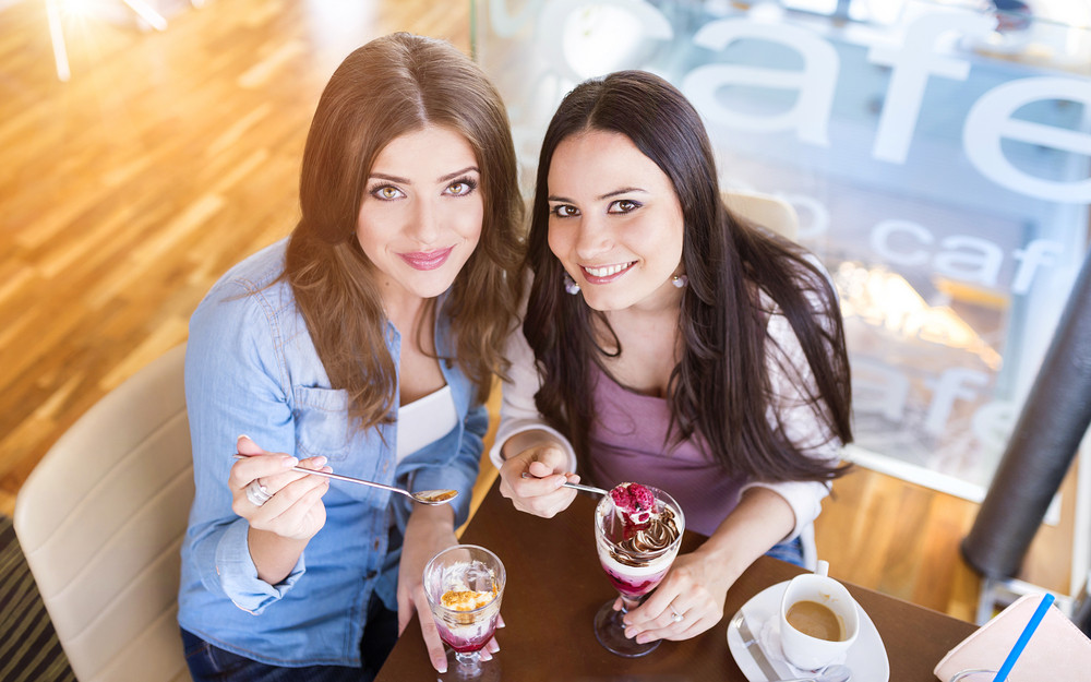 Two young beautiful women sitting in cafe
