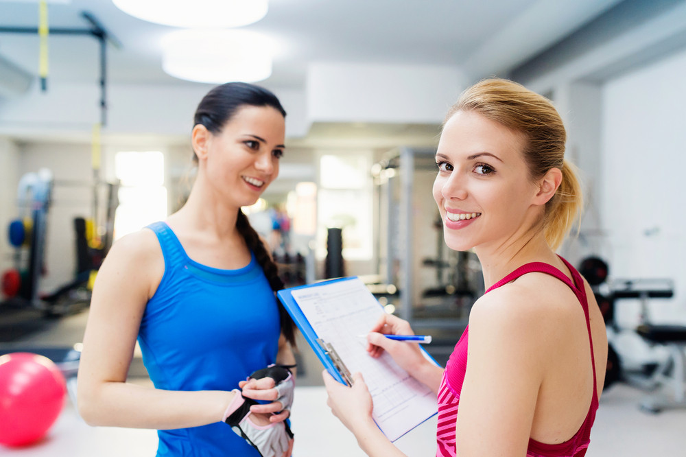 Two young beautiful women working out in gym