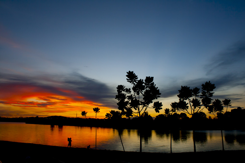 Two young boys on the lake, sunset.