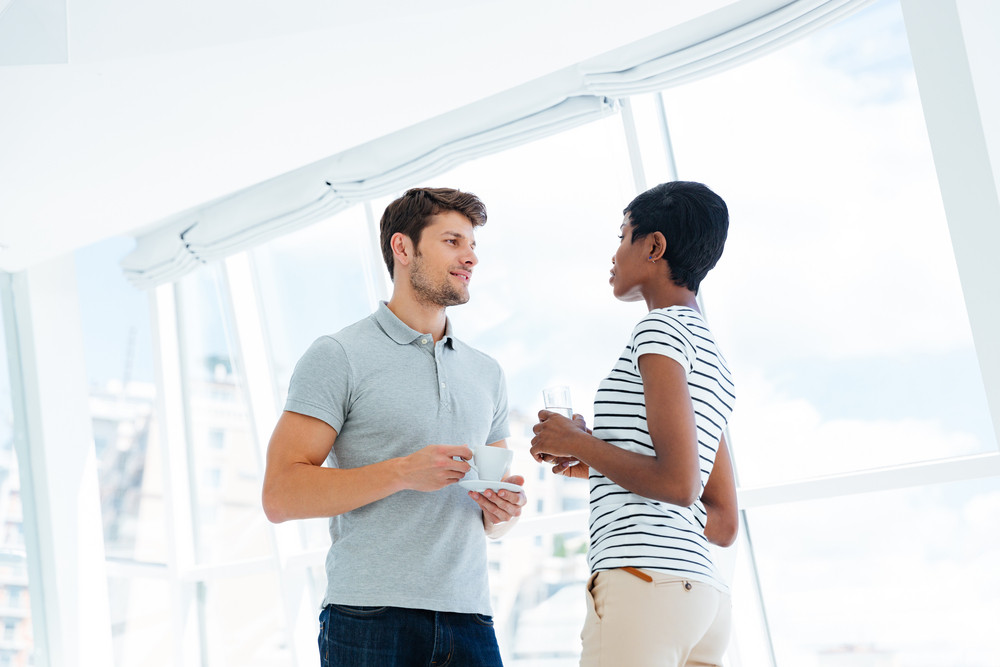 Two young business people standing and talking in office during coffee break
