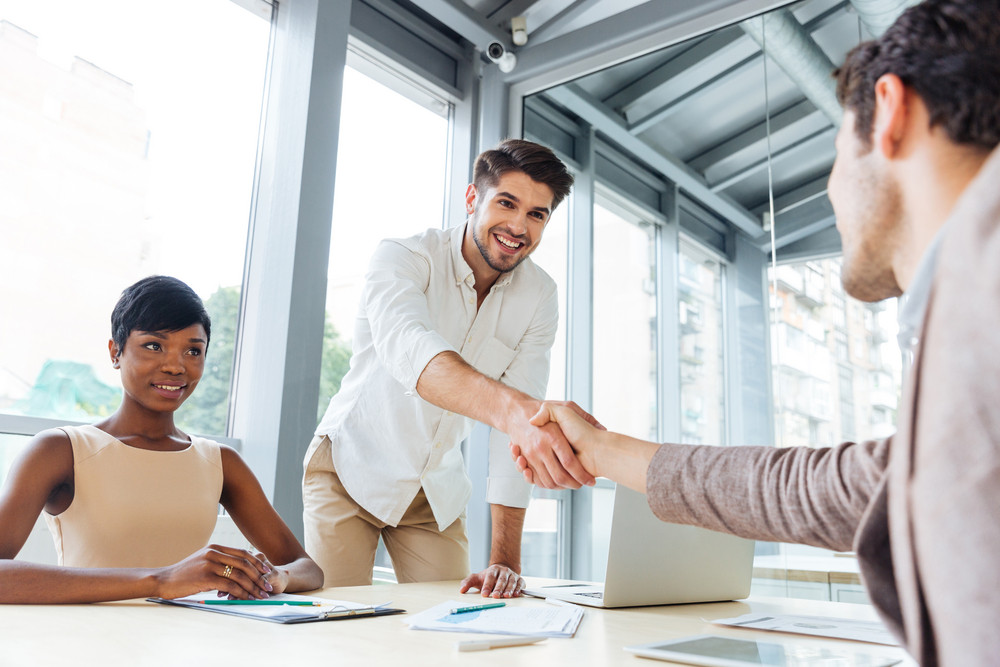two young businessmen shaking hands and ending business meeting in