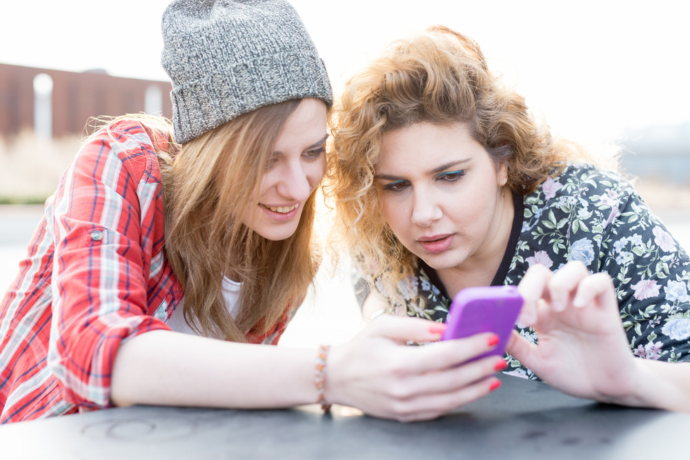 Two young curly and straight blonde hair caucasian woman sitting on a bar, using smartphone, both looking downward and tapping the screen - technology, social network, communication concept