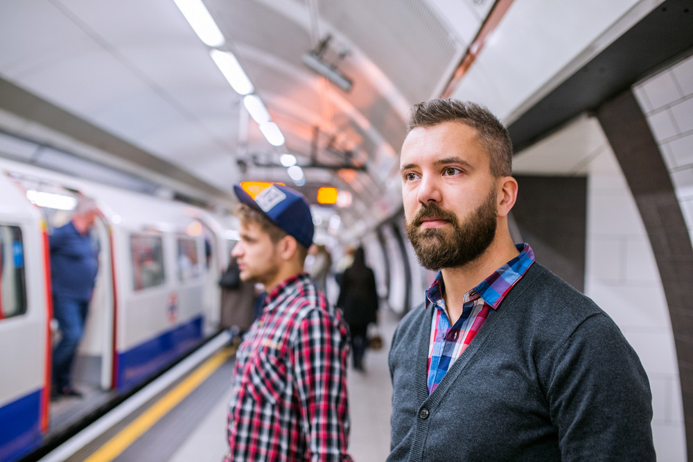Two young hipster men standing at the underground platform waiting
