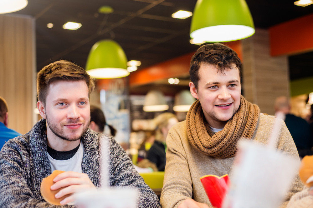 Two young men eating out in fast food restaurant, talking, having fun