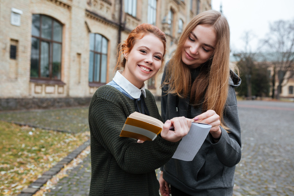 Two young smiling female classmates reading book outside the campus