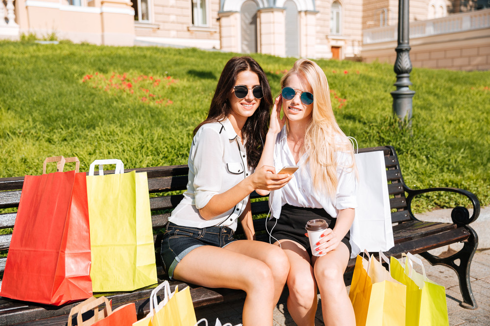 Two young women resting on the bench and listening music with earphones after shopping