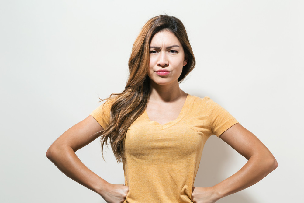 Unhappy young woman on a off white background