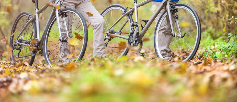 Unrecognizable active seniors having walk with bike in autumn nature. They having romantic time outdoor.