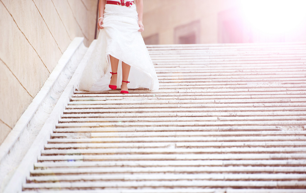 Unrecognizable beautiful young bride outside running down the stairs