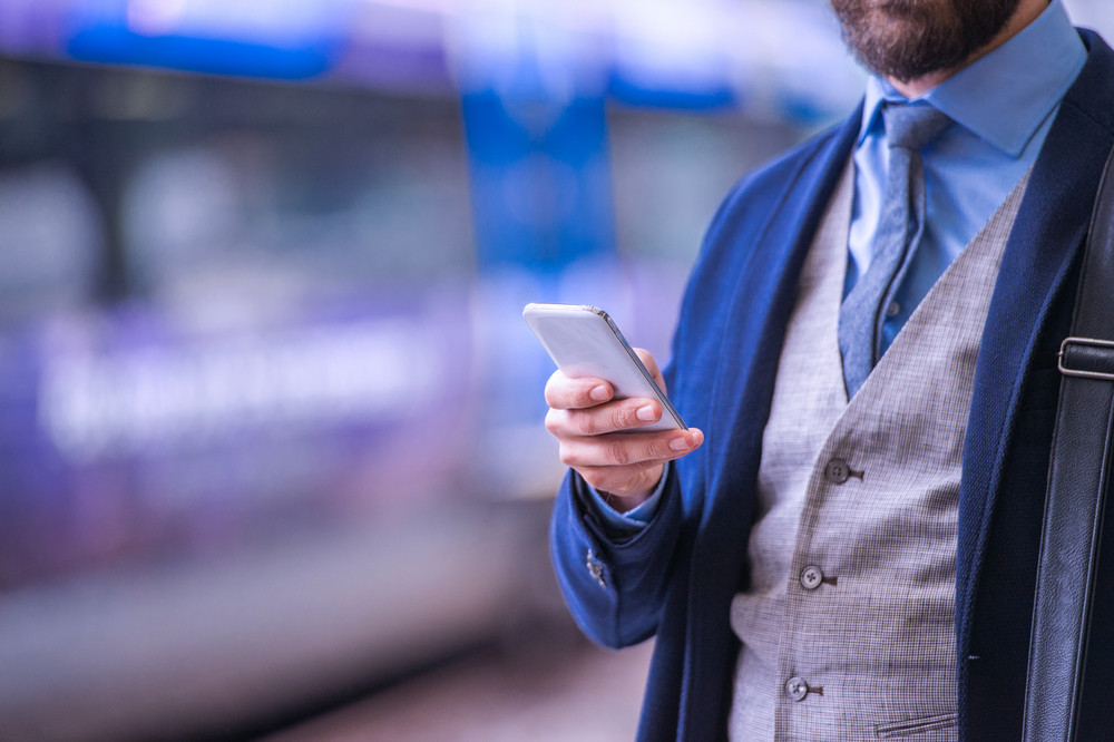 Unrecognizable businessman with smartphone, waiting at the train station platform