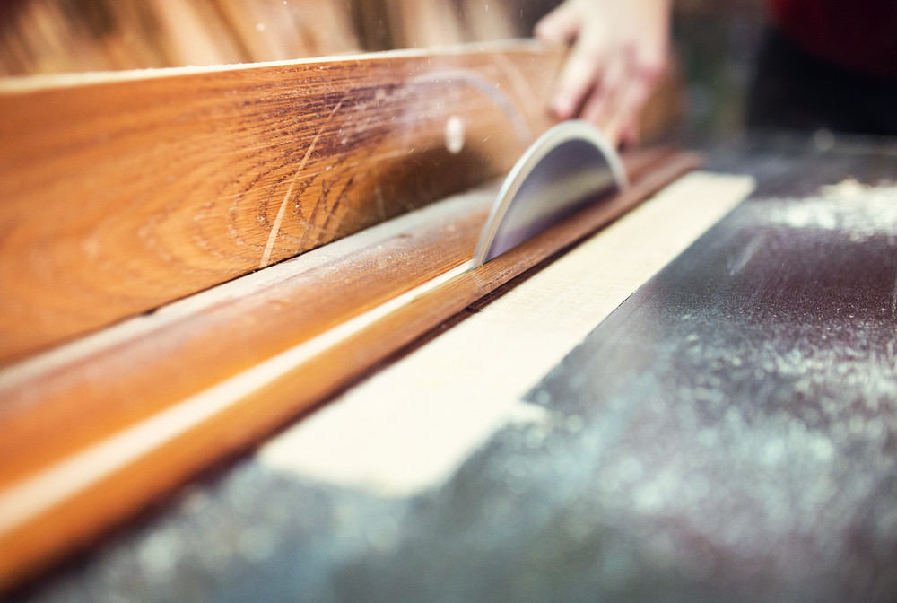 Unrecognizable carpenter cutting wooden planks with table saw