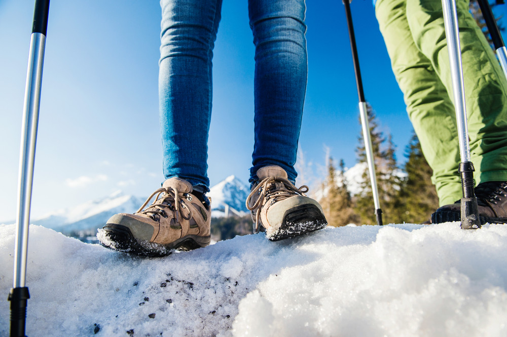 Unrecognizable couple hiking outside in sunny winter mountains