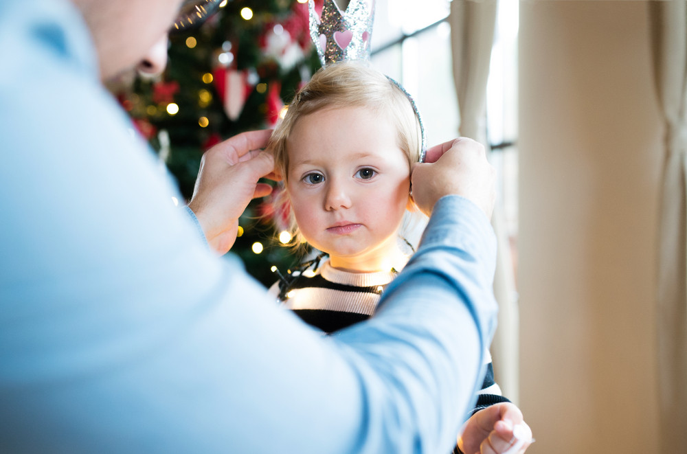 Unrecognizable father at Christmas tree giving her cute little daughter crown.