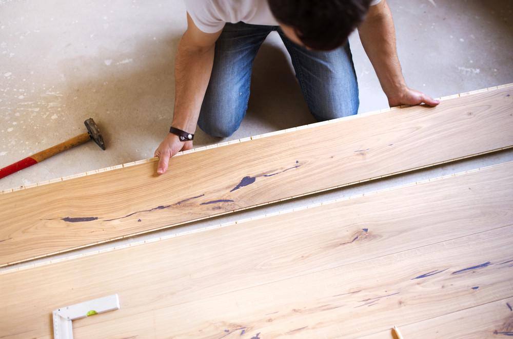 Unrecognizable handyman installing wooden floor in new house