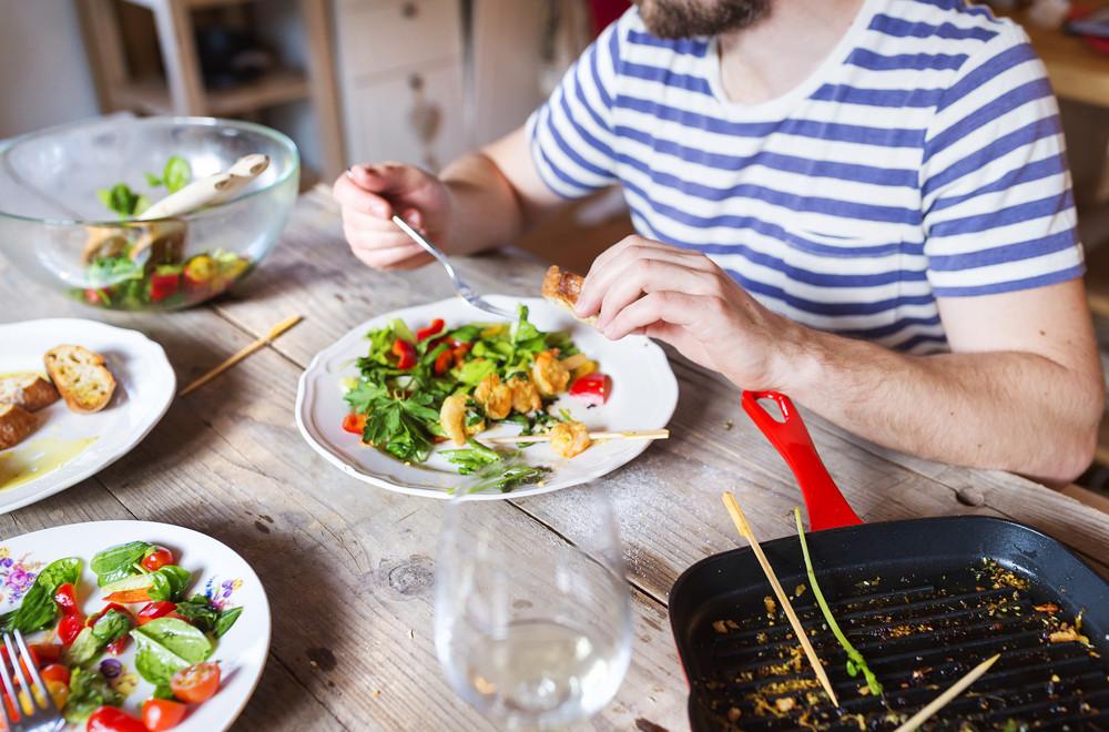 Unrecognizable man eating prawns, salad and bread together