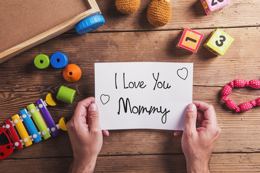 Unrecognizable man holding I love you mommy sign. Mothers day composition. Various toys. Studio shot on wooden background.